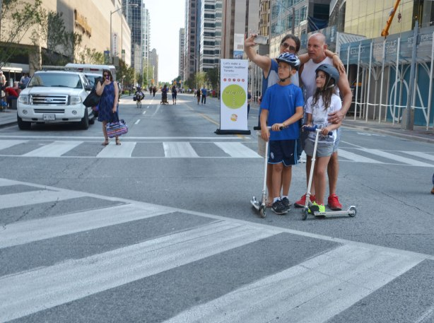 A family of four is in the intersection of Yonge and Bloor on the Sunday of Open Streets when the street was closed to traffic. The kids are on scooters.