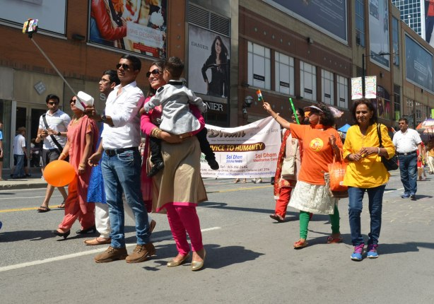 An Asian man (India heritage) is taking a picture of his family with a selfie stick as they walk in a parade down Yonge Street. His wife is holding a child. Other are walking behind them and holding a banner.