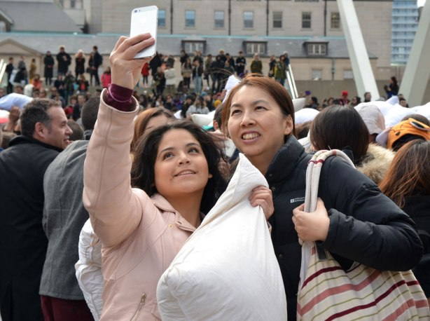 Two women are standing together as they take a selfie at Nathan Phillips Square during the pillow fight that was held there. One woman is holding a phone, the other woman is holding a pillow.
