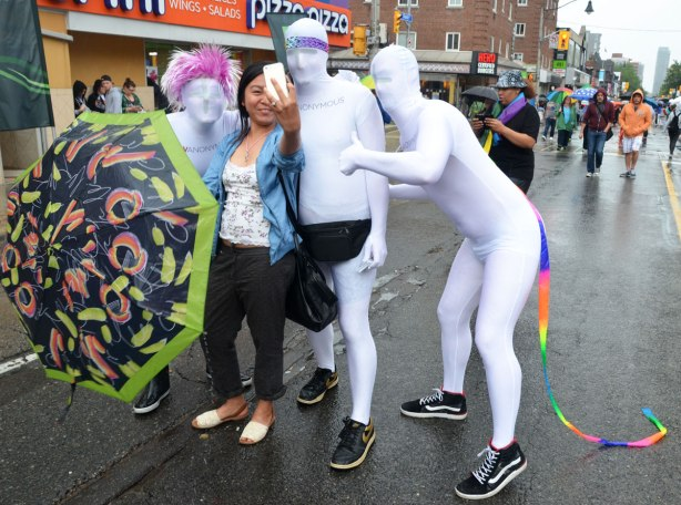 A woman with a brightly coloured umbrella is taking a selfie with three people at the Pride Parade in Toronto. The people are dressed from head to tow in white as part of an HIV awareness campaign, HIV is anonymous (and so are the people totally covered in white)