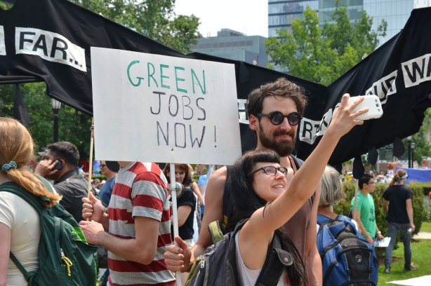 A couple is taking a selfie at a protest march. SOmeone is holding a sign that says Green Jobs Now behind them.