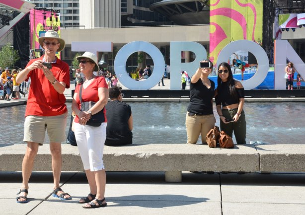 A couple dressed in red and white are taking a selfie beside each other in front of the 3D Toronto sign at Nathan Phillips square. Two other people are to the right, also taking pictures. They could be taking a selfie or their camera could be pointed away from them.