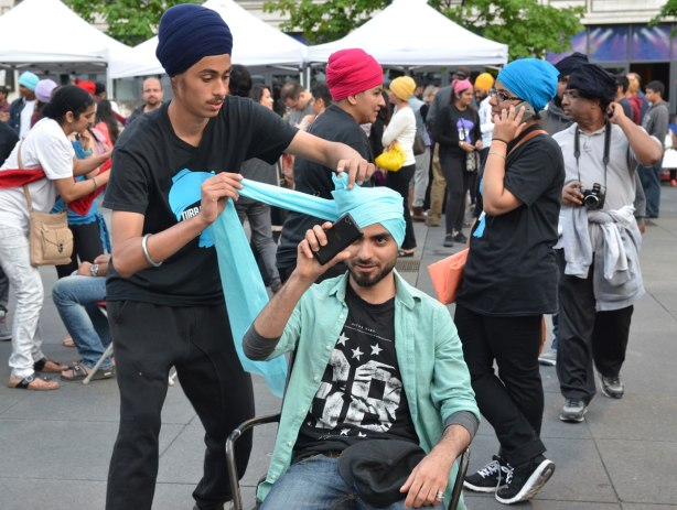 A man is taking a selfie as another man wraps his head in a light blue turban.