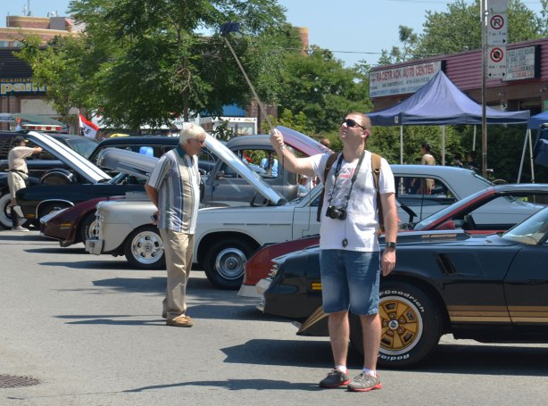People taking selfies - a man with a selfie stick at a car show on the Danforth. He is standing in front of a row of cars with their front hoods up.