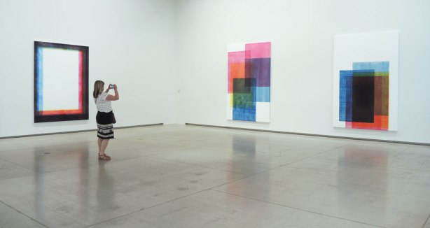 A room in an art gallery with white walls and three large paintings on it. A woman is taking a picture of one of them with a camera. The paintings consist of large rectangles