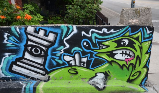 a low concrete fence is painted with graffiti street art, a green snarling green raccoon creature is acting out against a chess piece, a castle or rook