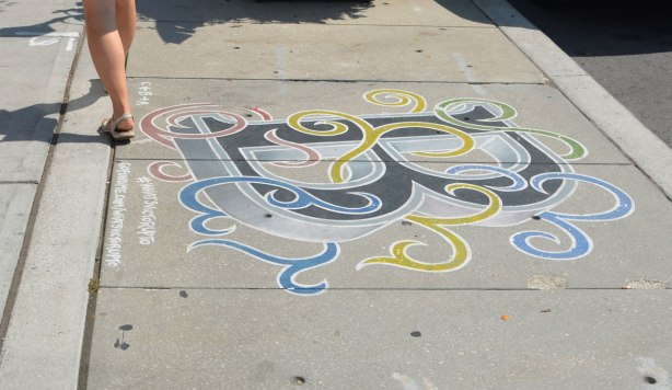 The letter B is painted on a sidewalk in black, with blue, gree, yellow and swirls like ribbons wrapped loosely around the letter