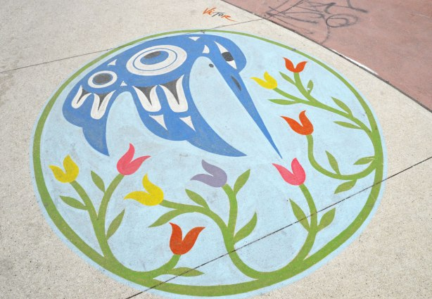 A painting on a sidewalk of a hummingbird done in Inuit style in blue and white, also some flowers, all enclosed in a green circle.