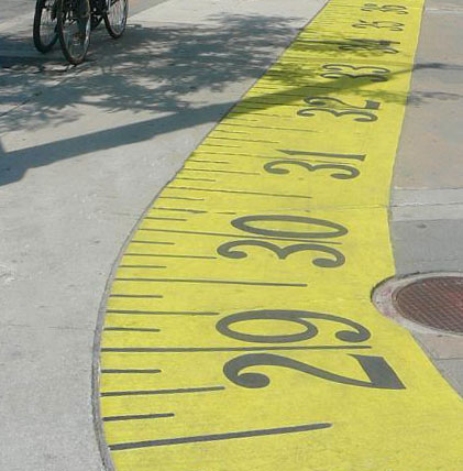 Part of a yellow tape measure that has been painted on a sidewalk in Toronto