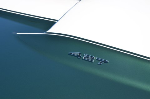 part of the hood of a green and white car with the number 427 on it
