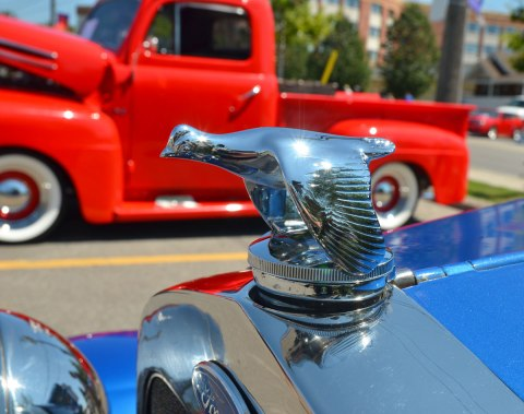 photo taken at a car show - hood ornament on a blue ford that is the shape of a bird with it's wings partially down, in the background is on old red truck.