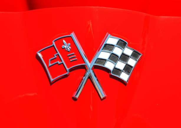 picture taken at a car show - detail of the hood badge of a red car, two crossed flags, one red and one checkered