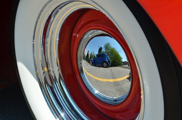 reflection of a blue vintage car in the hubcap of an old car, taken at a car show