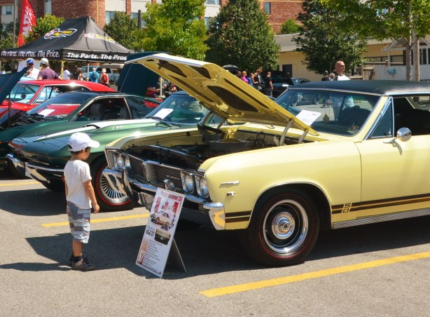 picture taken at a car show - a boy is standing in front of a yellow car with its front hood open. It is a Pontiac Beaumont SD