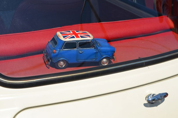 model car, blue Mini with roof painted as a Union Jack, on the back dash of an original British mini, photo taken from outside the car.