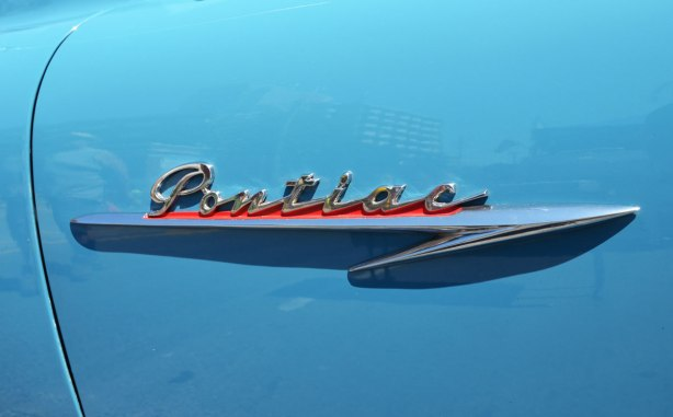 picture taken at a car show - the metal side ornament that says Pontiac in script that is on a light blue car