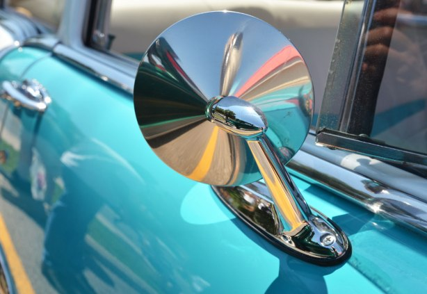 picture taken at a car show - the backside of a small round rearview mirror on a light blue car