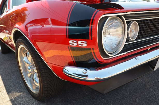 picture taken at a car show - the front corner of a red sports car showing wheel and front head lamps