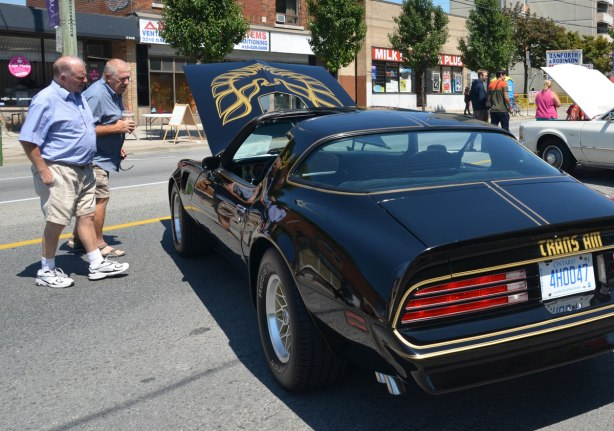 picture taken at a car show - two men are talking together and looking under the hood of a black Trans Am