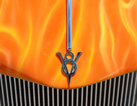 V8 hood ornament made to look like an arrow on the hood of a car that has been painted yellow and orange