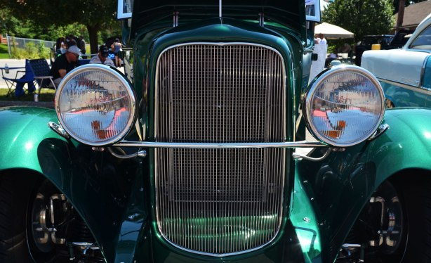 picture taken at a car show - front of an old green car (1930 Model A Ford), showing two round head lamps and a large metal radiator grille
