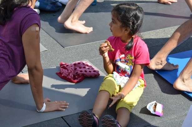 men and women at a yogathon - doing yoga outside in a large group, young girl sitting on the ground and eating a cookie while her mother does yoga.