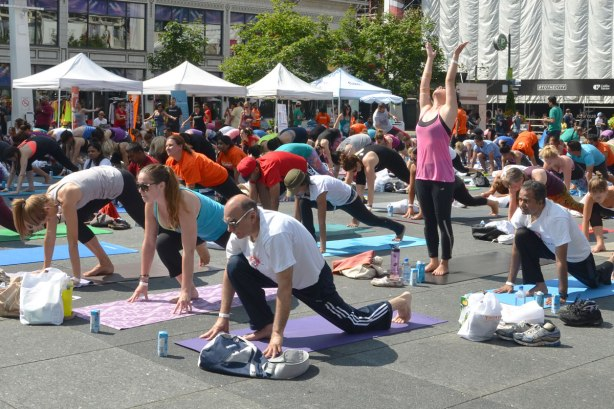 men and women at a yogathon - doing yoga outside in a large group - most people are in a lunge position except for one woman who is standing with her arms raised