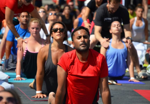 men and women at a yogathon - doing yoga outside in a large group, in downward dog position