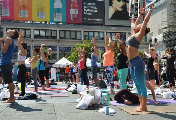 men and women at a yogathon - doing yoga outside in a large group