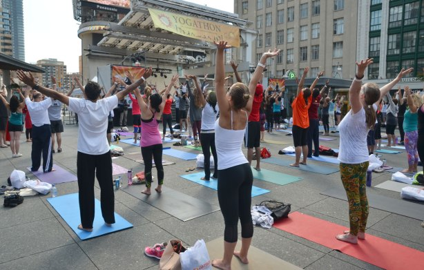 men and women at a yogathon - doing yoga outside in a large group - looking toward the stage where the leaders are, arms stretched upwards, YOnge Dundas Square in Toronto