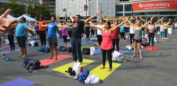 men and women at a yogathon - doing yoga outside in a large group - arms stretched to the side, standing, getting ready to practice yoga