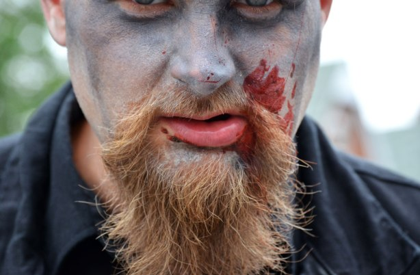 people dressed up as zombies - a man with a reddish beard, up close photo with only the bottom part of his eyes in the picture