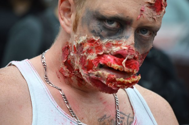 people dressed up as zombies - a man with black eyes and a chewed up face