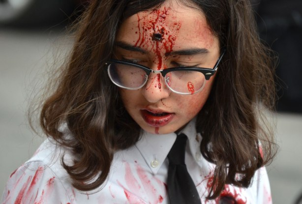 people dressed up as zombies - a woman with long hair and glasses, wearing a white shirt and black tie, with a bullet hole in her head.