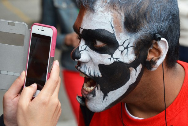 people dressed up as zombies - a young man with his face painted like a skull on one side, is screaming into a woman's smartphone as she takes a picture of him