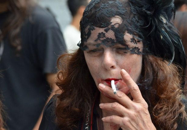 people dressed up as zombies - a woman with a black head scarf over the top of head and forehaed. She has long auborn hair and she's smoking a cigarette