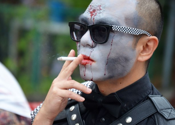people dressed up as zombies - a man with grey ashen face, red lips, wearing dark sunglasses and smoking a cigarette
