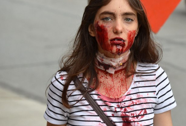people dressed up as zombies - a young woman with dead looking empty eyes and blood dripping from her mouth