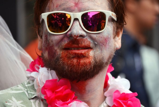 people dressed up as zombies - a man with a beard, bloody face, and white framed sunglasses. He is wearing a pink and white garland of fake flowers around his neck