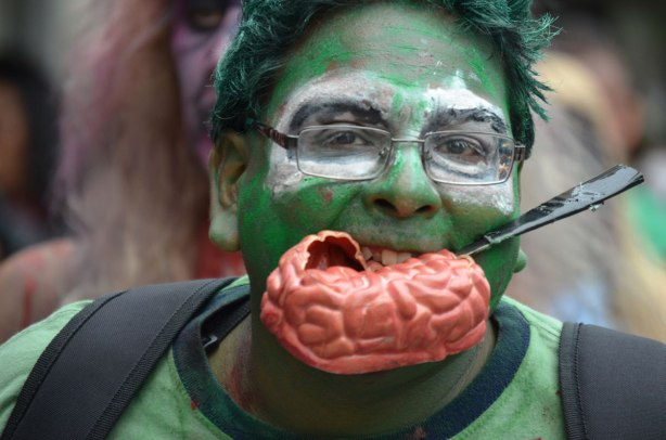 people dressed up as zombies - a very green faced zombie biting on brains, there is a knife stuck in the plastic brains too