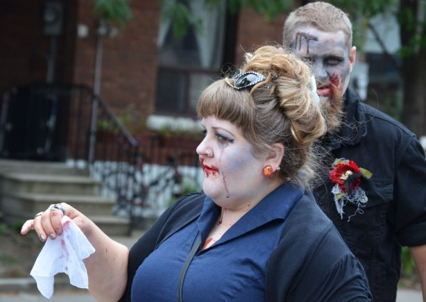 people dressed up as zombies - two zombies, a woman in a blue dress waving a white hanky and behind her a man looking directly at the camera
