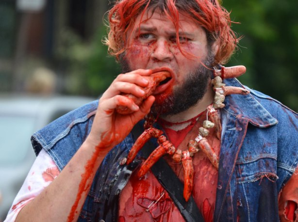 people dressed up as zombies - a man with a necklace made of fingers and bones, covered in blood as he munches on a finger.