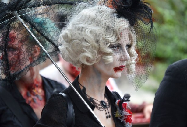 people dressed up as zombies - a woman with white wavy hair, black lacy parasol and black necklace