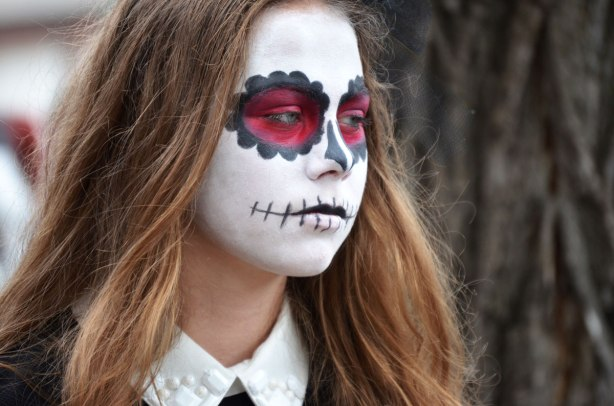 people dressed up as zombies - a young woman with white face, and mouth painted to look like it's been stitched together
