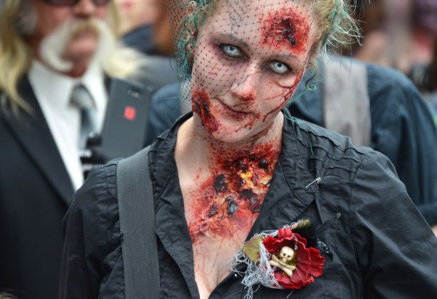 people dressed up as zombies - a woman dressed in black including lacey veil, Her chest is full of wounds and so is her forehead