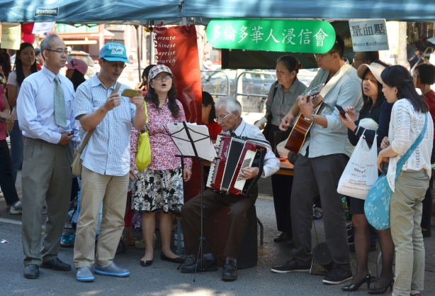members of the Toronto Chinese Baptist church making music, singers, accordian, and guitar player