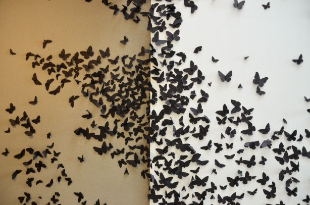 A wall covered with black paper moths, part of an art installation called Black Cloud by Carlos Amorales
