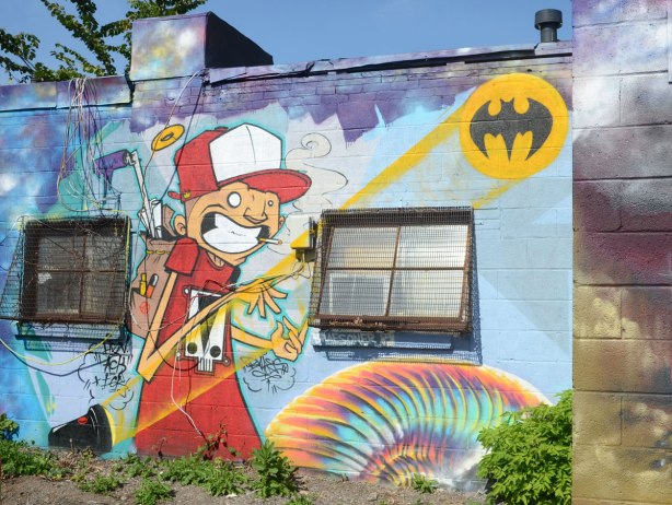 A street art by braes of a boy in a red and white baseball hat and red shirt. The bat signal is beamed onto the wall beside him, black bat symbol in a yellow oval. The boy has a backpack full of tools.