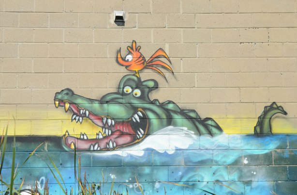 A crocdile swimming in the water with a little orange birdie sitting on his head - a street art painting on the side of concrete block wall. The croc is swimming in the water, with his mouth open wide and showing his teeth