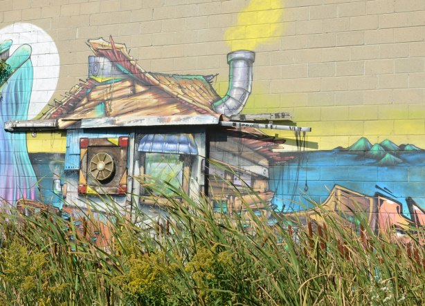 a street art painting of a makeshift boat with stove pipe smoke stack, painted to look like boat is made of boards haphazardly nailed together. On the the side of a building, but with weeds growing up in front of it.